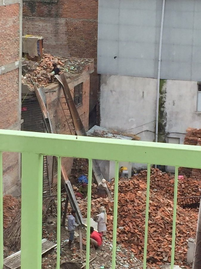 This was the scene happening across from the hotel.  Workers were in the process of salvaging bricks from the third floor by putting them into two piles.  The bricks that could be reused went down one slide, then workers on the ground pounded off the concrete from the brick to get it ready to use again.